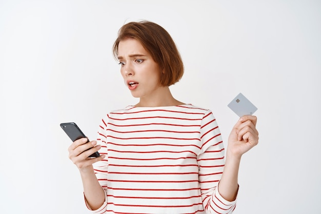 Bezorgde jonge vrouw die het smartphonescherm leest, een plastic creditcard vasthoudt, angstig en verward staat tegen een witte muur