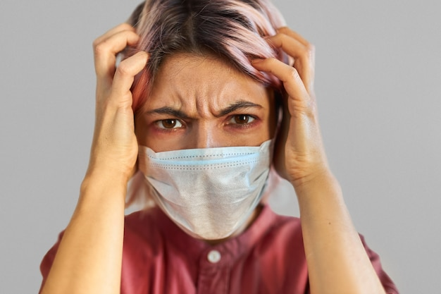 Bezorgde jonge vrouw in paniek die lijdt aan ernstige hoofdpijn, met covid-19-symptomen. benadrukt meisje in medisch gezichtsmasker bezorgd over besmettelijke luchtweginfectie of seizoensgriep