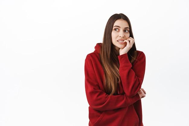 Bezorgde jonge vrouw met lang haar, vingernagels bijtend en peinzend opzij kijkend, nerveus denkend, moeilijke keuze makend, nadenkend tegen de witte muur staan