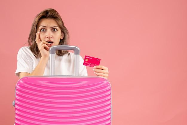 Bezorgde jonge vrouw met roze koffer met kaart