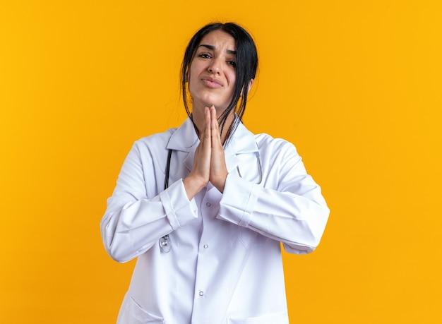 Bezorgde jonge vrouwelijke arts die een medisch gewaad draagt met een stethoscoop die een gebedsgebaar toont dat op een gele muur is geïsoleerd
