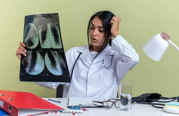 Bezorgde jonge vrouwelijke arts die een medisch gewaad met een stethoscoop draagt, zit aan het bureau met medische hulpmiddelen met röntgenstralen die de hand op het hoofd zetten geïsoleerd op de olijfgroene muur