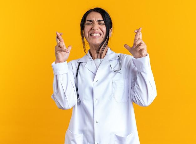 Bezorgde jonge vrouwelijke arts die medische mantel draagt met een stethoscoop die vingers kruist geïsoleerd op gele muur