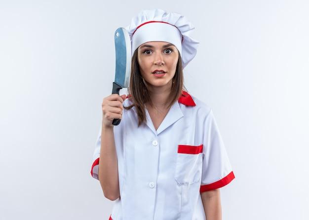 Bezorgde jonge vrouwelijke kok die chef-kokuniform draagt die hakmes houdt dat op witte muur wordt geïsoleerd
