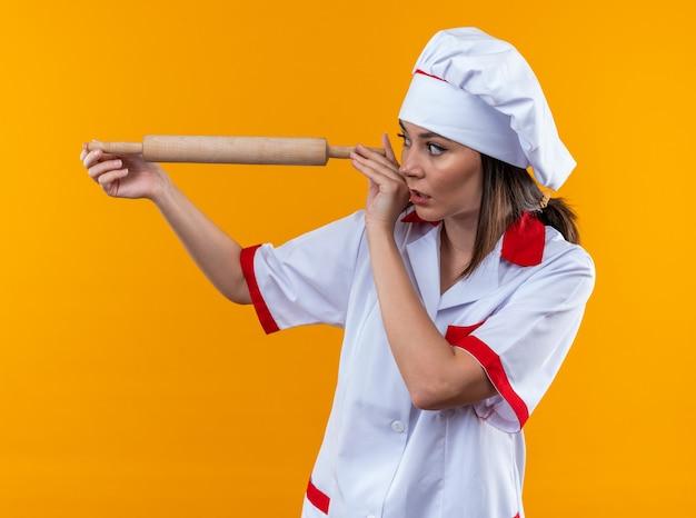 Bezorgde jonge vrouwelijke kok die een chef-kok uniform draagt en kijkt naar deegroller geïsoleerd op een oranje muur