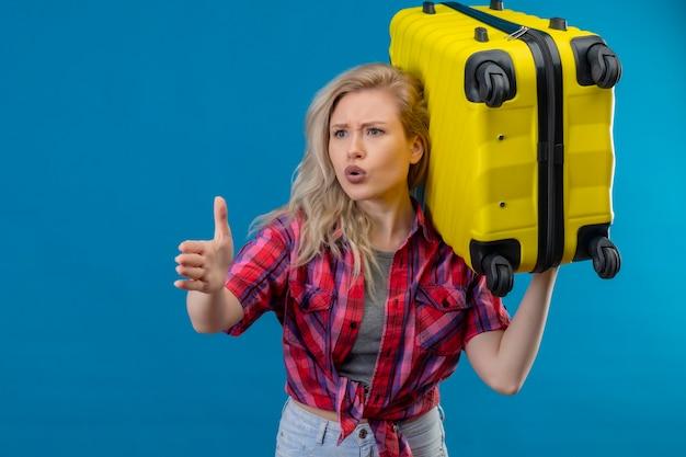 Bezorgde jonge vrouwelijke reiziger die de rode koffer van de overhemdsholding op schouder draagt wijst naar de zijkant op geïsoleerde blauwe muur