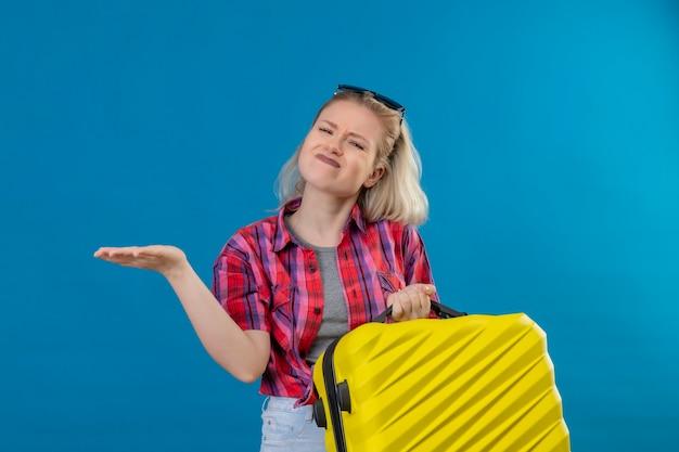 Bezorgde jonge vrouwelijke reiziger die een rood overhemd en een bril op het hoofd draagt en de koffer naar de andere kant wijst op geïsoleerde blauwe muur