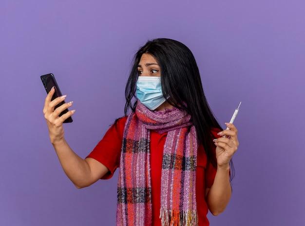 Bezorgde jonge zieke vrouw die masker en sjaal draagt die mobiele telefoon en thermometer houdt die telefoon bekijkt die op purpere muur wordt geïsoleerd