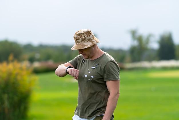 Bezorgde man in een t-shirt en slappe hoed staan kijken naar zijn polshorloge in een groen landelijk park terwijl hij verwachtingsvol wacht op iemand die arriveert