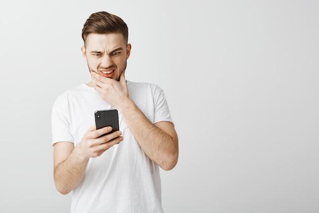 Bezorgde man ineenkrimpen op smartphoneweergave, angstig op zoek naar mobiele telefoon
