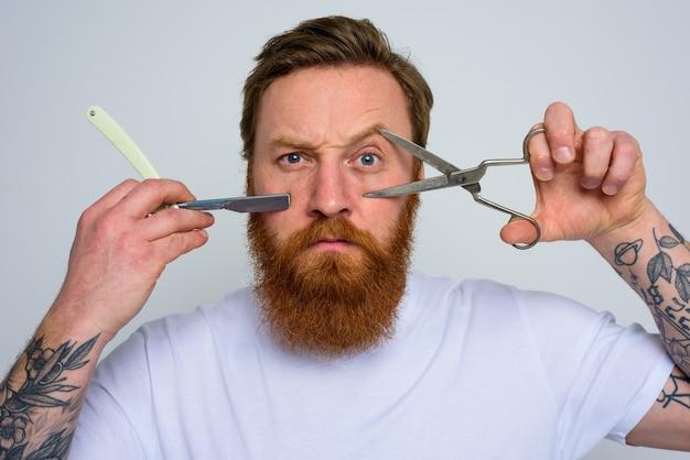 Bezorgde man met schaar en mes is klaar om de baard te knippen