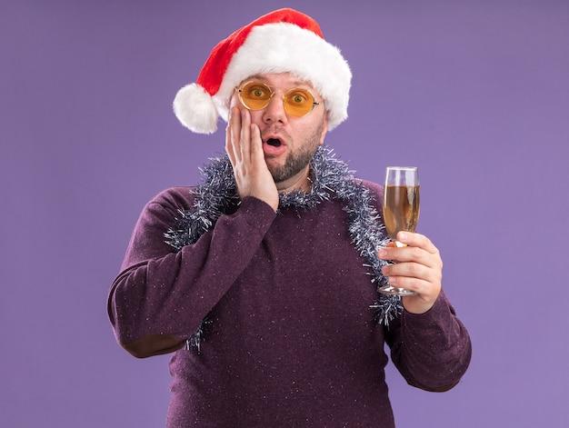 Bezorgde man van middelbare leeftijd met kerstmuts en klatergoud slinger rond de nek met een glas champagne houden de hand op het gezicht geïsoleerd op paarse muur