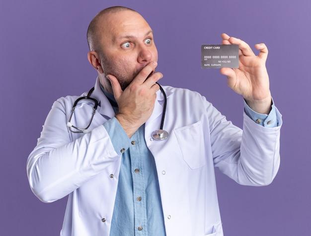 Bezorgde mannelijke arts van middelbare leeftijd die een medisch gewaad en een stethoscoop draagt en naar een creditcard kijkt die de hand op de mond houdt geïsoleerd op de paarse muur