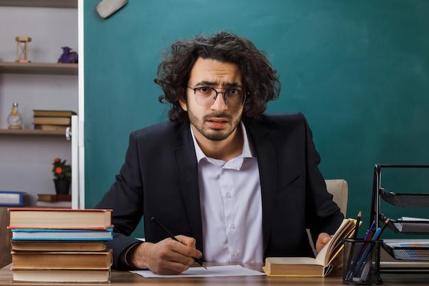 Bezorgde mannelijke leraar die een bril draagt, schrijft iets op papier dat aan tafel zit met schoolgereedschap in de klas