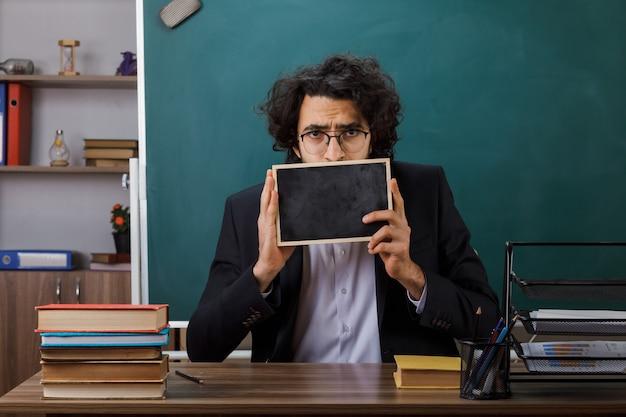 Bezorgde mannelijke leraar met een bril die een bedekt gezicht vasthoudt met een mini-bord aan tafel met schoolgereedschap in de klas