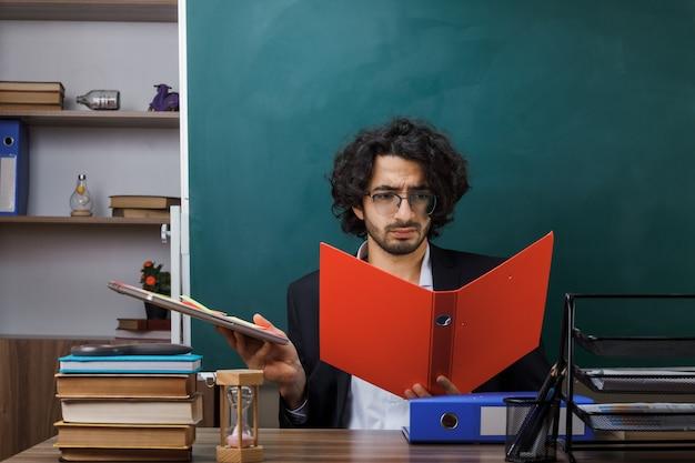 Bezorgde mannelijke leraar met een bril die een map vasthoudt en bekijkt die aan tafel zit met schoolhulpmiddelen in de klas