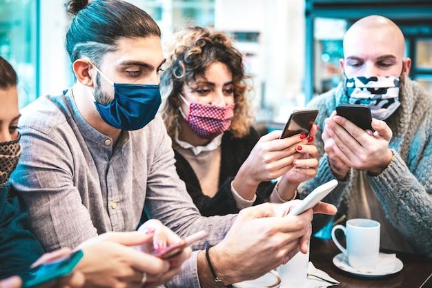 Bezorgde mensen die met gezichtsmasker nieuws op mobiele smartphones controleren tijdens koffiepauze