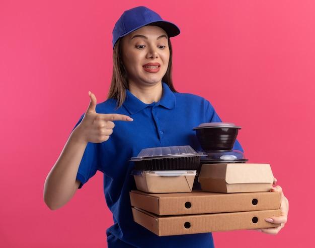 Bezorgde mooie bezorger in uniform houdt en wijst naar voedselpakket en containers op pizzadozen op roze