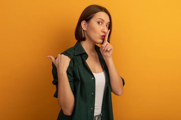 Bezorgde mooie blanke vrouw doet stilte gebaar en punten aan de zijkant op oranje