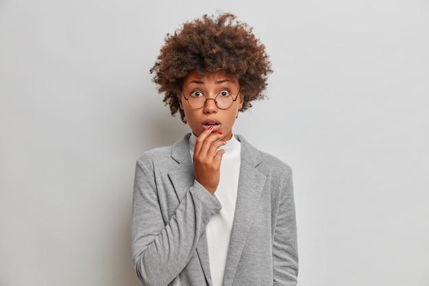 Bezorgde nerveuze vrouwelijke ondernemer houdt de adem in tijdens lastig moment, houdt de hand op de lippen, draagt formele kleding