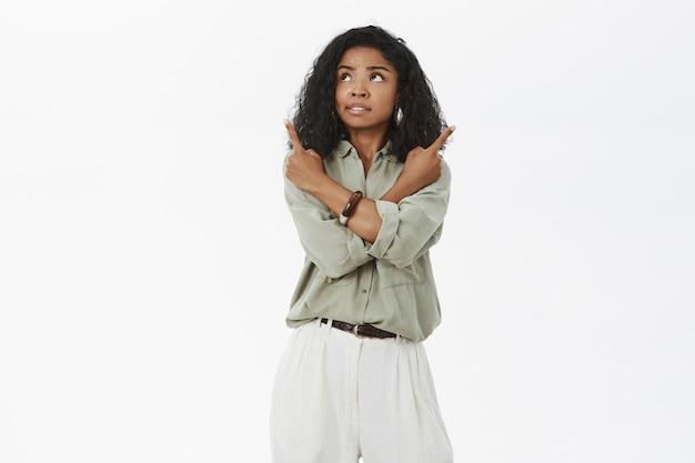 Bezorgde onrustige aantrekkelijke afro-amerikaanse volwassen vrouw met krullend kapsel die zich onzeker voelt terwijl ze de armen kruist op het lichaam en in verschillende richtingen wijst