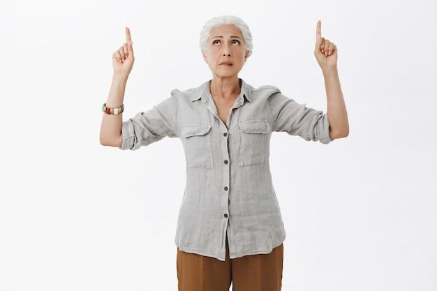 Bezorgde oude vrouw met grijs haar die er nerveus uitziet en de vingers omhoog wees