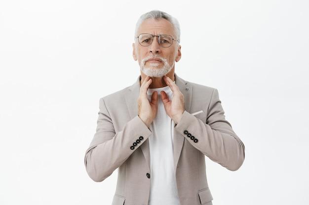 Bezorgde oudere man raakt zijn nek aan en klaagt keelpijn