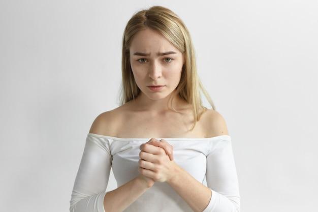 Bezorgde peinzende jonge blonde vrouw met losse haarstijl die handen wrijft, een ongemakkelijke blik heeft, zich zorgen maakt over haar kinderen, probeert te concentreren en te kalmeren. lichaamstaal