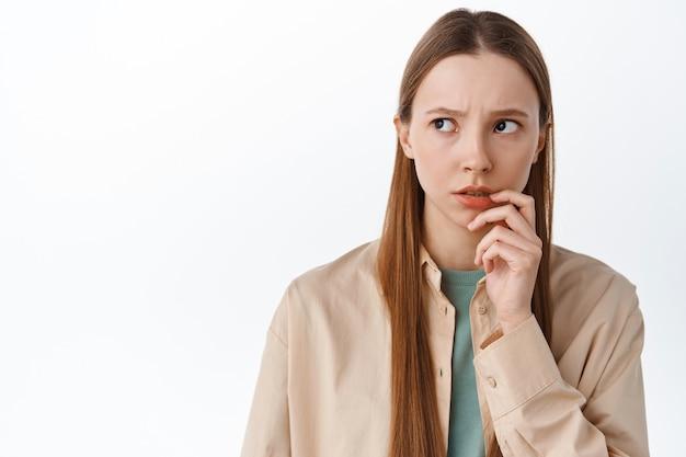 Bezorgde peinzende tienerstudent kijkt opzij, raakt de lip nerveus aan en denkt na, staat angstig of aarzelend tegen de witte muur