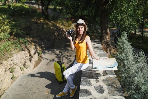 Bezorgde reiziger toeristische vrouw in gele kleding hoed met koffer stadsplattegrond met retro vintage fotocamera buiten. meisje dat naar het buitenland reist om een weekendje weg te reizen. toeristische reis levensstijl.