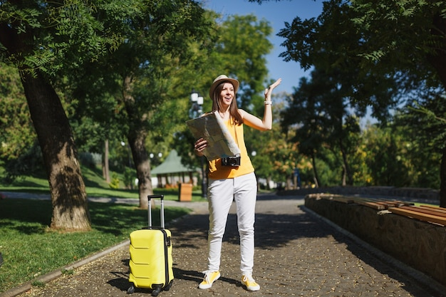 Bezorgde reiziger toeristische vrouw in hoed met koffer en stadsplattegrond spreidende handen wegkijkend wandelen in de stad buiten. meisje dat naar het buitenland reist om een weekendje weg te reizen. toeristische reis levensstijl.