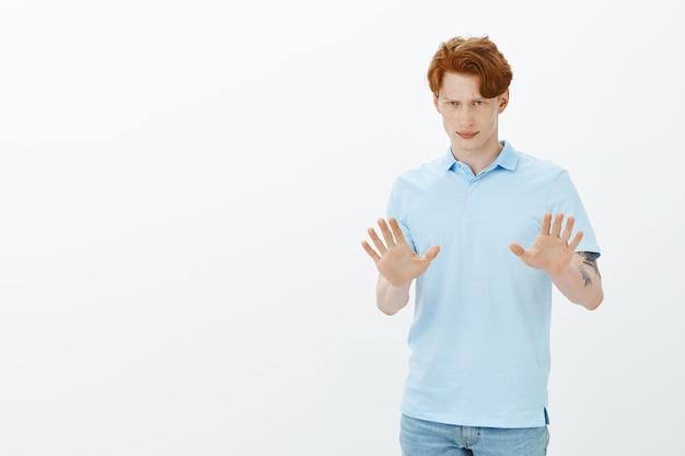 Bezorgde roodharige man probeert situatie op te lossen, kalmeert, hand opsteken om argument op te lossen