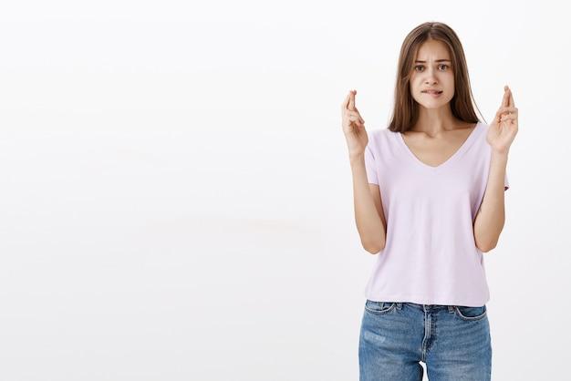 Bezorgde schattige vrouwelijke brunette in de hoop dat ze geslaagd is voor examens om naar de universiteit te gaan.ze droomt ervan op onderlip te bijten en te fronsen.ze kijkt intens haar vingers kruisen voor geluk terwijl ze een wens doet