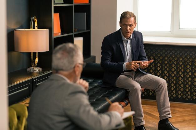 Bezorgde serieuze man die over zijn persoonlijke problemen vertelde aan zijn psychoanalyticus in zijn kantoor