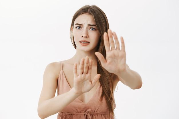 Bezorgde timide en onzekere bezorgde vrouw die stopgebaar doet