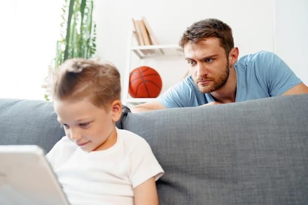 Bezorgde vader gluren naar wat zijn zoon op digitale tablet kijkt