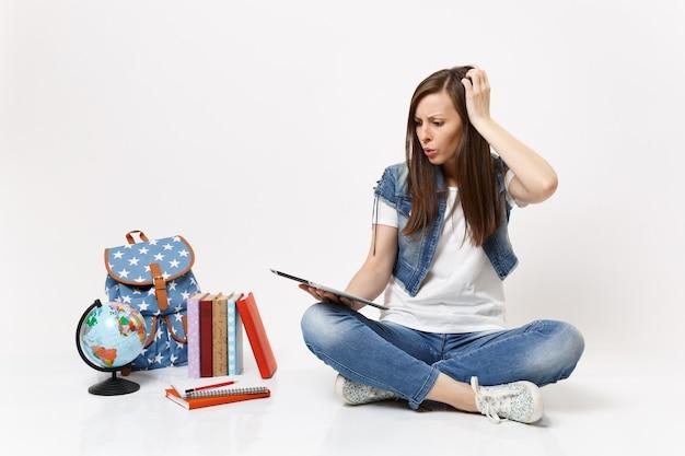 Bezorgde, verbaasde vrouwelijke student die tablet-pc-computer gebruikt, zich vastklampt aan het hoofd, in de buurt van een globe-rugzak zit, schoolboeken geïsoleerd