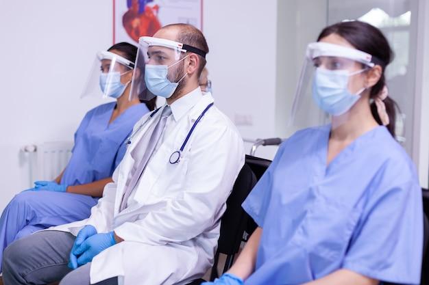 Bezorgde volwassen arts die in de wachtkamer van de ziekenhuiskliniek zit met een medisch verpleegkundig team dat naar de camera kijkt met een chirurgisch gezichtsmasker tegen covid 19-infecties