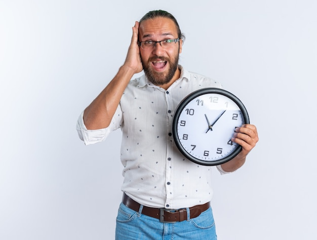 Bezorgde volwassen knappe man met een bril die de hand op het hoofd houdt en de klok vasthoudt terwijl hij naar de camera kijkt die op een witte muur is geïsoleerd
