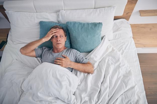 Bezorgde volwassen mannelijke persoon die in een knus bed ligt en naar het raam kijkt terwijl hij diep in gedachten is