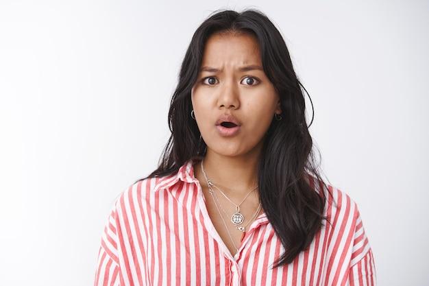 Bezorgde vriendin die verontrustend nieuws hoort empathie en medelijden voelen bezorgd en overstuur staan fronsen met open mond, medelijden hebben met de vreselijke situatie die gebeurt tegen een witte muur staan