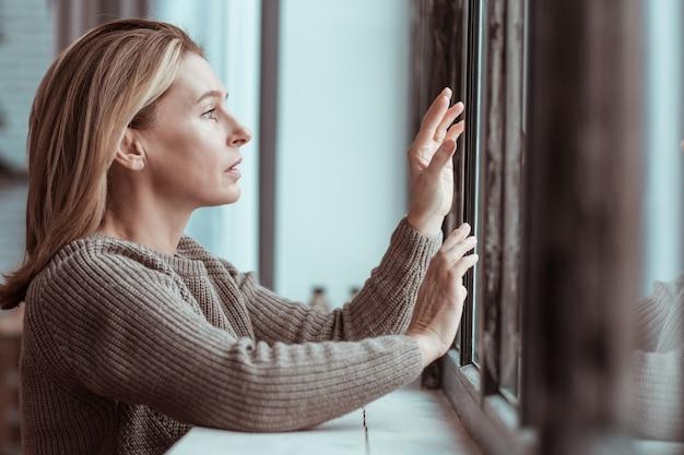 Bezorgde vrouw. bezorgde volwassen vrouw met blond haar die bij het raam staat en zich depressief voelt