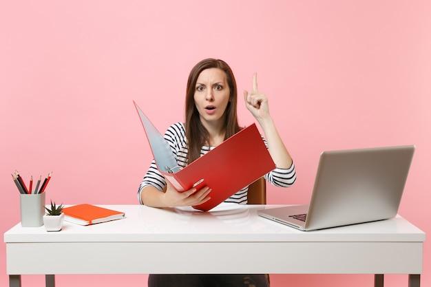 Bezorgde vrouw die met de vinger omhoog wijst en de map met papieren documenten vasthoudt, werkt aan een project terwijl ze op kantoor zit met een laptop