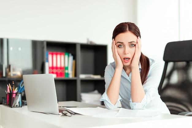 Bezorgde vrouw in het kantoor bezorgd over het bedrijfsleven