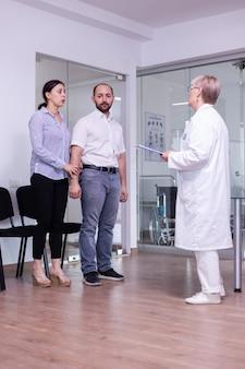 Bezorgde vrouw kijkt naar dokter die wacht op medische resultaten