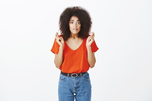 Bezorgde vrouw met afrokapsel poseren in de studio