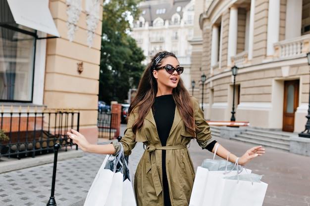 Bezorgde vrouw met veel tassen na het winkelen en wegkijken