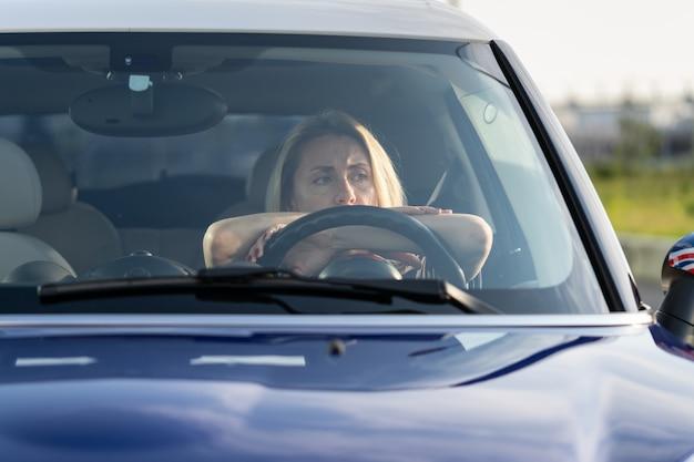 Bezorgde vrouw op bestuurdersstoel van auto die niet rijdt, kijkt door voorruit en denkt aan geldcrisis