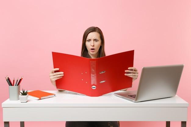 Bezorgde vrouw op zoek op rode map met papieren documenten, bezig met project zittend op kantoor met laptop geïsoleerd op pastel roze achtergrond. prestatie zakelijke carrière concept. ruimte kopiëren.