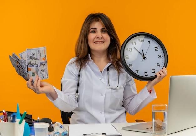Bezorgde vrouwelijke arts van middelbare leeftijd die medische mantel met stethoscoop draagt die aan bureau werkt op laptop met medische hulpmiddelen die contant geld en muurklok op geïsoleerde oranje muur met exemplaarruimte houdt